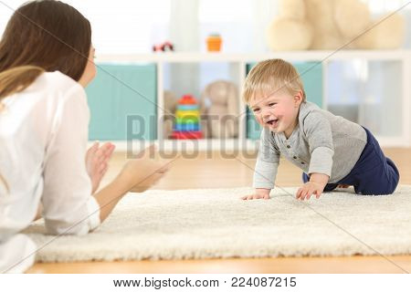 Happy baby crawling towards his mother on a carpet at home