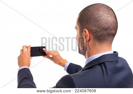 Rear view of handsome businessman take a selfie of himself with smartphone, isolated on a white background