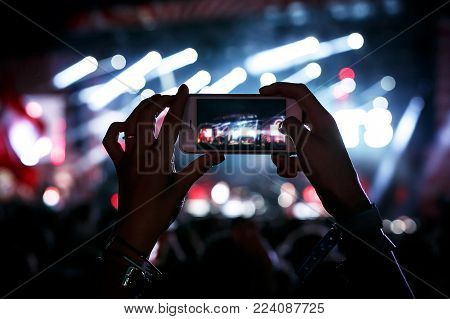 Hands with a smartphone records live music festival, Taking photo of concert stage, live concert