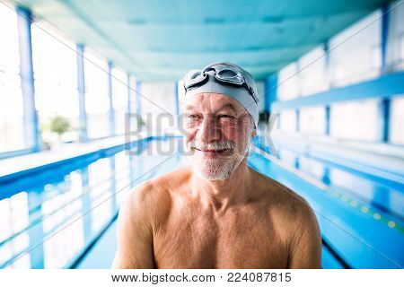 Senior man standing in an indoor swimming pool. Active pensioner enjoying sport.