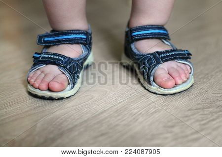 Shod legs of the baby. Children's sandals on their feet. Toddler shoes. Tourist sandals for the smallest travelers. A new purchase in a shoe store.