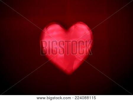 Big red Blur heart shape of ligth bokeh on a black background.