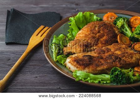 Chicken steak in breadcrumbs with vegetables on a plate. Menu, restaurant concept. Served in.