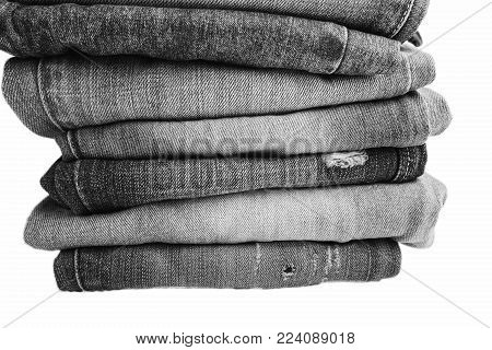 Stack of folded clothes, blue jeans pants, dark blue denim trousers isolated on white background