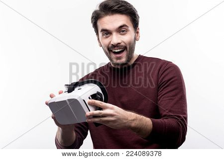 Happy about purchase. Charming upbeat young man in a burgundy sweater holding his new VR headset and smiling at the camera while standing isolated on a white background