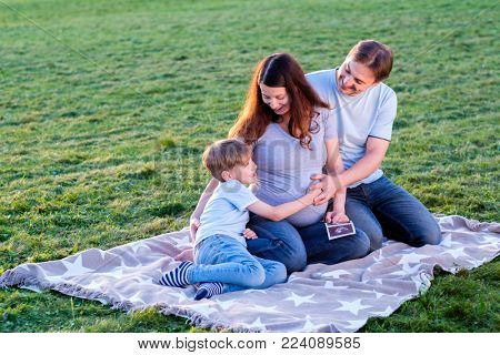 Happy pregnant family of three expecting new baby. Father and mother with little boy hugging outdoors.