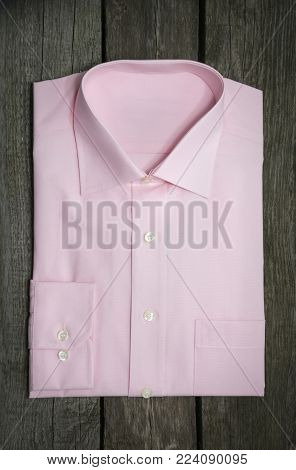 New pink shirt and pen on wooden background. Top view.