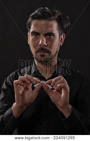Portrait of adult man who is decided to quit smoking. Low key effect on image is intentional.