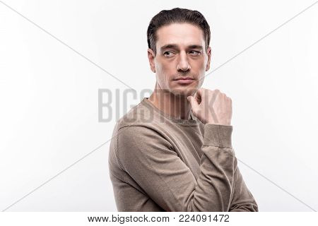 Masculinity incarnate. Charming middle-aged man standing half-turned and posing for the camera, raising his arm and looking into the distance