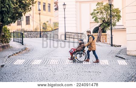 Father in wheelchair and young son on a walk., crossing the road. A carer assisting disabled senior man.