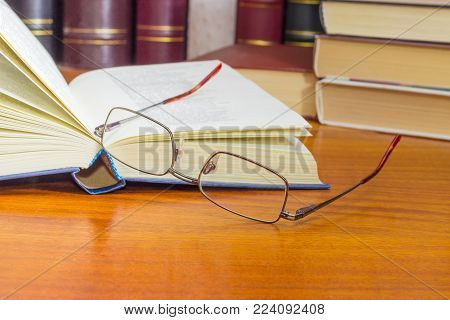 Classic mens eyeglasses and open book in blue hardcover on a wooden table closeup against of the other books at selective focus