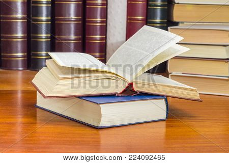 Open book with red hardcover lying on closed book with blue hardcover on a wooden table at selective focus with blurred text against of the other books on the background