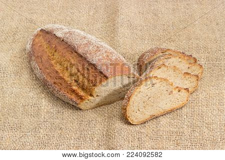 Partly sliced oval loaf of the wheat and rye sprouted bread with added whole sprouted wheat grains, rye malt and molasses, baked in the hearth on a sackcloth