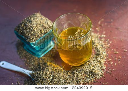 Black Cumin Seeds,shah Jerra,nigella Sativa  And Its Extracted Water In A Transparent Glass On Brown
