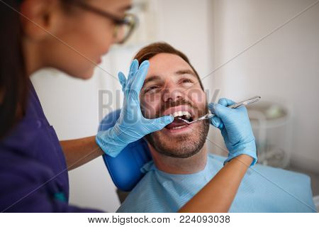 Dentist checking up patients teeth with dental mirror in ordination