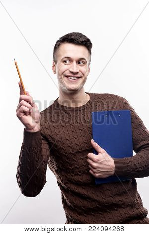 Upbeat office worker. Cheerful young man in a brown sweater posing with a pencil and a blue sheet holder while smiling and standing isolated on a white background