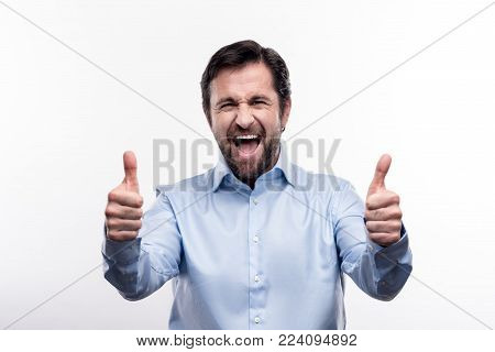 Content person. Upbeat handsome middle-aged man showing thumbs up with his both hands and grinning while posing isolated on a white background