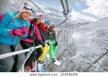 smiling friends are lifting on ski-lift for skiing in the mountains