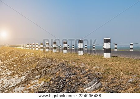 Milestones,black And White Milestones With Green Grass Roadside,lake Roadside In Background,concept