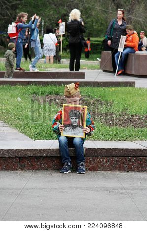 Volgograd, Russia - May 09, 2017: Boy holds portrait of their relative in the action
