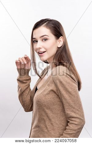 Cute model. The portrait of a charming young woman standing half-turned and posing for the camera, raising one hand, while chuckling