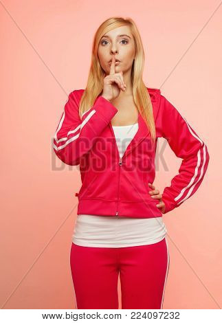 Secret woman. Sporty fit fitnrss blonde girl showing hand silence sign, saying hush be quiet on pink background
