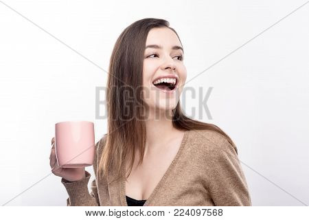 Absolutely energetic. Upbeat adorable young woman holding a pink cup of coffee and laughing, looking into the distance, while posing against white background