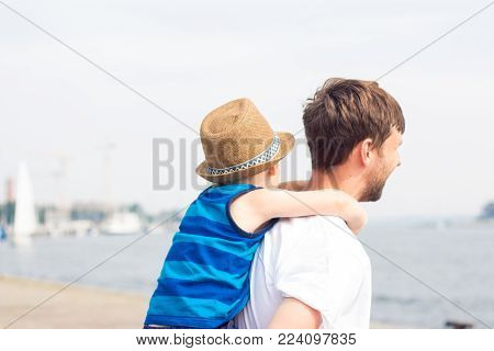 Dad and son on the beach. Ocean. Summer. Happy dad and son are walking, looking at boats. Spring.
