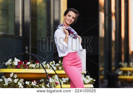 Young fashion business woman walking in city street Stylish female model in white blouse and pink pencil skirt at office building