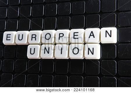 European union control text word title caption label cover backdrop background. Alphabet letter toy blocks on black reflective background. European union.