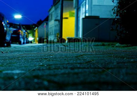 Walkway in a city with a narrow focus on the cobblestones and downtown out of focus in the background, shallow focus gradient and blue, cold colors with yellow.