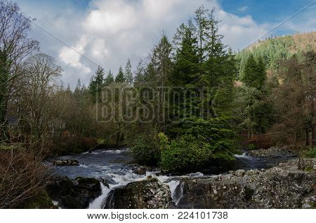 Beautiful river scene with trees on a small island and a waterfall in the foreground at the village of Betws Y Coed in North Wales