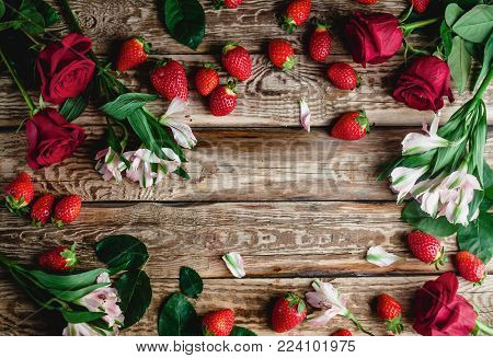 top view of fresh strawberries and flowers on wooden shabby background, valentines background