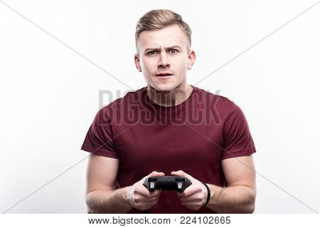 Focused on playing. Charming fair-haired young man holding a video game controller and playing a game, being focused