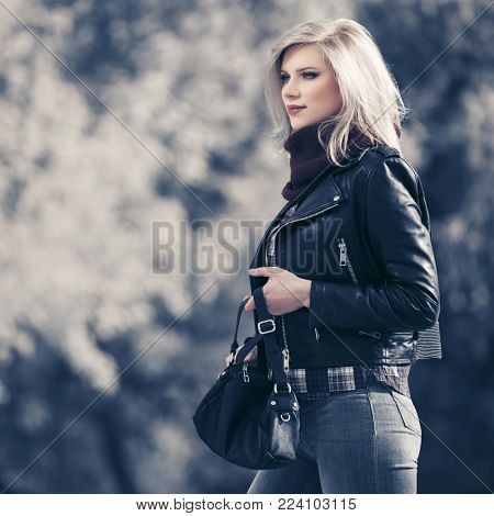 Young fashion blond woman walking in city park Stylish female model in black leather jacket outdoors