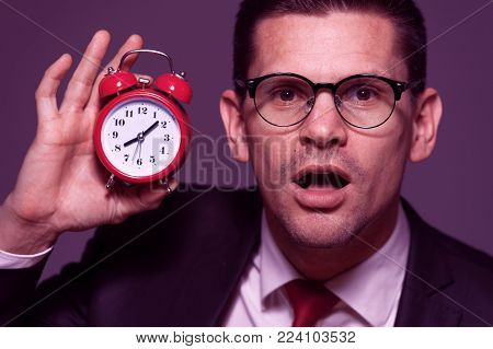 Concept in purple tone - portrait of handsome businessman wearing glasses and formal attire with an amazed face and holding clock