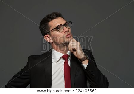 Thoughtful businessman with glasses and formal attire ponders about shares and growing exchange rate looking somewhere far away on a gray background. Copyspace