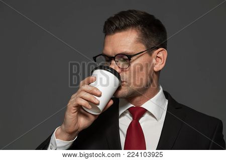 Close-up - young male manager in formal attire and glasses is drinking coffee on gray background