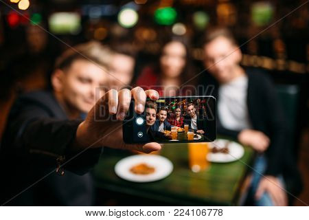 Fun friends makes selfie on phone in a sport bar