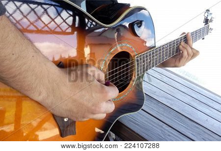 Guitar in the hands of a guitarist a chord with a barre correct grip of a mediator nature background music guitar and nature  country folk song from acoustic guitar man holding his guitar