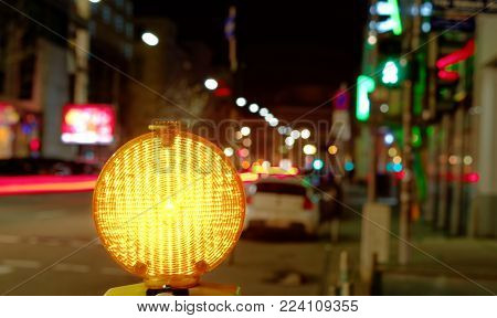 Construction site lamp at a construction site at night with flowing traffic in the background