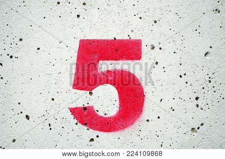 Five red numbers on old concrete and white backgrounds.