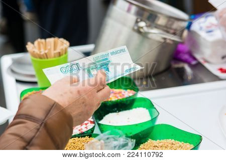 Close up hand holding paper money at a counter with desserts on market