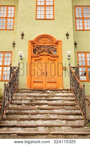 Old buiding entrance with metallic handrails and wooden door in Oslo, Norway.