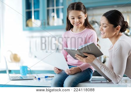 My dear mom. Pretty cheerful dark-haired girl smiling and holding while sitting on the table and her mum standing near her and showing a book