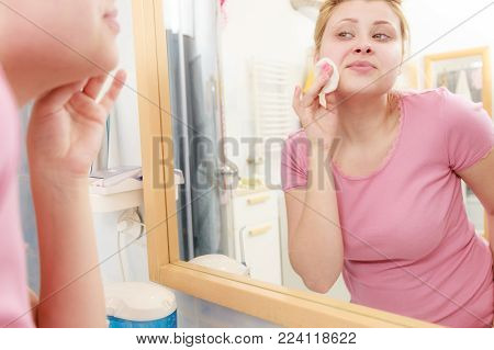 Skin complexion care concept. Young woman using cotton pad to remove make up or dirt from face.