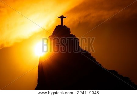 Rio de Janeiro, Brazil - January 17, 2018: The famous Rio de Janeiro landmark - Christ the Redeemer statue on Corcovado mountain. Silhouette by sunset.