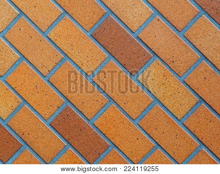 Paved brick background photograph, glazed brown on diagonal slant. Paved glazed bricks background, authentic photograph shot outdoors with natural light. Shades of brown and tan on a 45 degree left leaning slant.