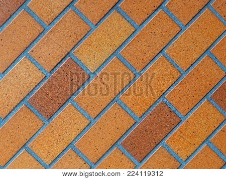 Paved brick background photograph, glazed brown on diagonal slant. Paved glazed bricks background, authentic photograph shot outdoors with natural light. Shades of brown and tan on a 45 degree right leaning slant.