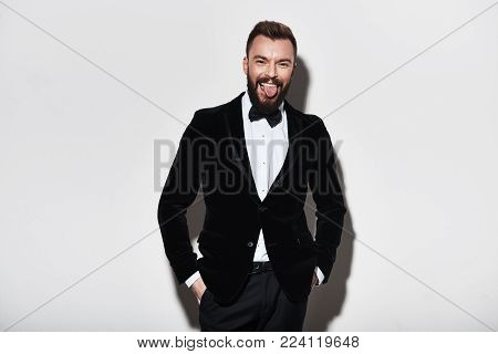 No rules. Playful young man in full suit sticking out tongue and looking at camera while standing against grey background